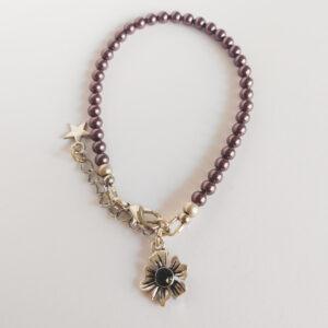 Armband swarovski parel 4 mm rood paars. Een armband met 4 mm swarovski pareltjes in een rood paarse kleur. Bij het slotje hangt een bedeltje in de vorm van een bloem met een swarovski steentje erin in de kleur jet, een zwarte kleur.