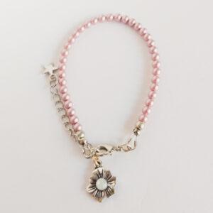 Armband swarovski parel 4 mm roze. Een armband met 4 mm swarovski pareltjes in een roze kleur. Bij het slotje hangt een bedeltje in de vorm van een bloem met een swarovski steentje erin in de kleur opal white, een melk witte kleur.