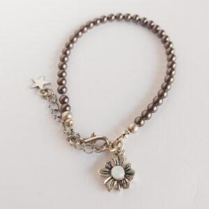 Armband swarovski parel 4 mm bruin. Een armband met 4 mm swarovski pareltjes in een bruine kleur. Bij het slotje hangt een bedeltje in de vorm van een bloem met een swarovski steentje erin in de kleur opal white, een melk witte kleur.