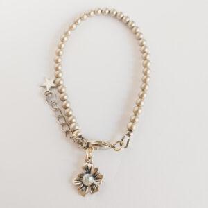 Armband swarovski parel 4 mm platinum. Een armband met 4 mm swarovski pareltjes in een platinum kleur. Bij het slotje hangt een bedeltje in de vorm van een bloem met een swarovski steentje erin in de kleur opal white, een melk witte kleur.