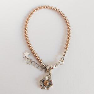 Armband swarovski parel 4 mm koper. Een armband met 4 mm swarovski pareltjes in een koper kleur. Bij het slotje hangt een bedeltje in de vorm van een bloem met een swarovski steentje erin in de kleur peach.