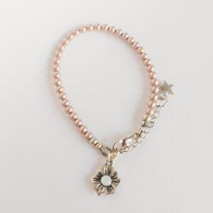 Armband swarovski parel 4 mm licht bruin. Een armband met 4 mm swarovski pareltjes in een licht bruine kleur. Bij het slotje hangt een bedeltje in de vorm van een bloem met een swarovski steentje erin in de kleur opal white, een melk witte kleur.