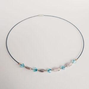 Ketting spang oval glaskralen licht blauw. Een spang van gecoat staaldraad met facet geslepen glaskralen in een licht blauwe kleur en metalen oval kraaltjes. Het slotje is een draaislotje.
