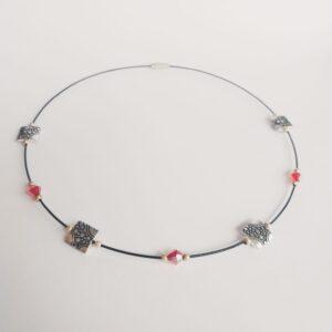 Ketting zwarte spang circles verspreide glaskralen rood. Een zwarte spang van gecoat staaldraad met verspreide facet geslepen glaskralen in een rode kleur en metalen circles kraaltjes. Het slotje is een draaislotje.