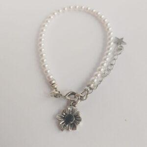 Armband swarovski parel 4 mm wit. Een armband met kleine 4 mm swarovski pareltjes in een witte kleur. Met een metalen bedeltje in de vorm van een bloem met een jet (zwart) swarovski steentje.