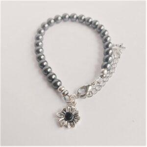 Armband swarovski parel 6 mm grijs. Een armband met 6 mm swarovski parels in een grijze kleur. Bij het slotje hangt een bedeltje in de vorm van een bloem met een swarovski steentje erin in de kleur zwart.