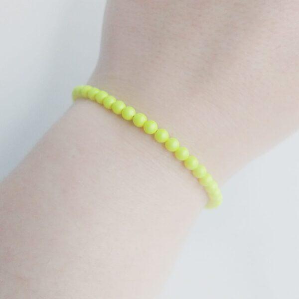 Armband swarovski parel neon geel. Een armband met kleine 4 mm swarovski pareltjes in een neon gele kleur. Bij het slotje hangt een bedeltje in de vorm van een vleugel. De armband wordt getoond om de pols van een blanke vrouw.