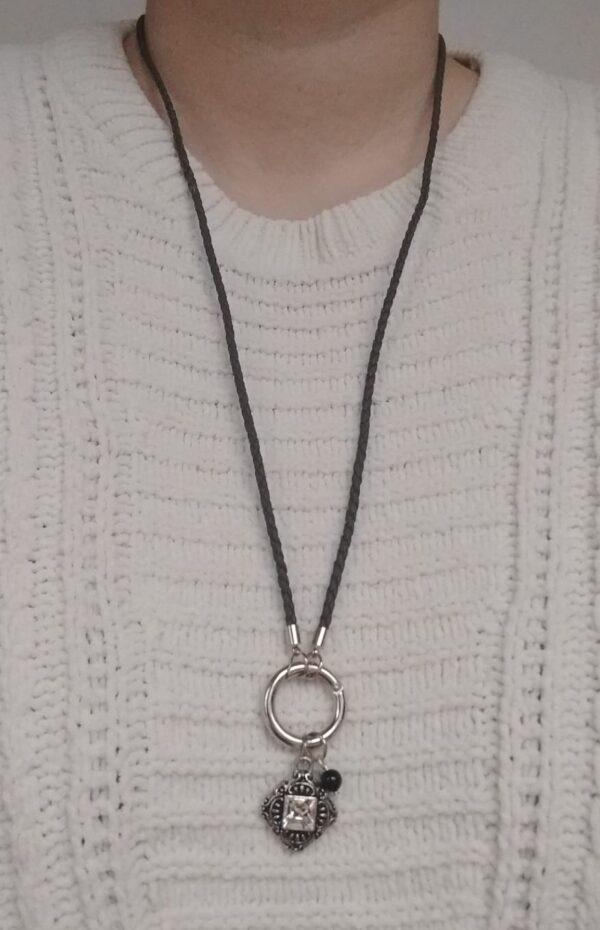 Ketting grijs leer clip-ring romantic square swarovski kristal. Grijze gevlochten leren ketting met een metalen clip-ring met een vierkante bedel met een vierkante swarovski steen in de kleur crystal, een kristal kleur. Er hangt een zwarte swarovski parel aan. De leren ketting is 76 cm lang. De ketting wordt getoond om de hals van een blanke vrouw met een witte gebreide trui aan.