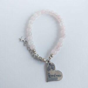 """Armband natuursteen rose quartz roze. Armband met 6 mm natuursteen rose quartz kralen, mooie roze kralen. Met een hart vormige metalen bedel bij het slotje met een willekeurige tekst erop. (Bijvoorbeeld """"Kindness"""" of """"Joy"""") Er zit een verlengkettinkje aan zodat de armband verstelbaar is tot verschillende maten. Aan het einde van het verlengkettinkje hangt nog een klein metalen sterretje."""