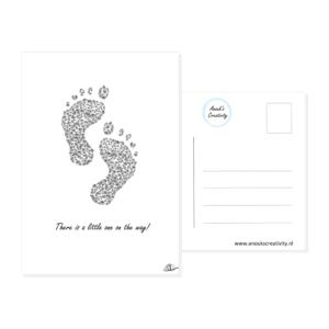 """Ansichtkaart little one on the way. Ansichtkaart met 2 baby voetafdrukjes gemaakt uit bloemen in zwart wit. Daaronder staat de tekst """"A little one on the way!"""" De achterkant van de ansichtkaart is ook te zien, daarop staan lijntjes voor het adres en is er plaats voor een postzegel."""