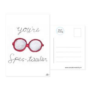 """Ansichtkaart spec-tacular. Een ansichtkaart met handgemaakte illustraties van een rode bril. De tekst daaromheen is """"You're spec-tacular"""". Op de foto is de kaart tegen een muur te zien met een plantje ernaast."""