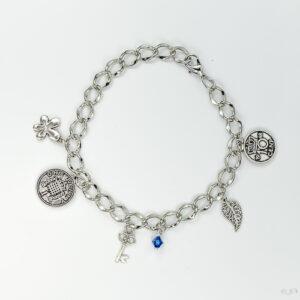 Armband schakels bedels swarovski blauw. Armband met grote schakels. Met swarovski kraaltjes in de kleur capri blue, een blauwe kleur. Met verschillende bedeltjes. Er zit een verlengkettinkje aan zodat de armband verstelbaar is tot verschillende maten. De armband wordt getoond op een witte achtergrond.