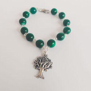 Armband boom bedeltje glaskraaltjes groen. Armband met glaskraaltjes in een groene kleur en een bedeltje in de vorm van een boompje. Er zit een verlengkettinkje aan zodat de armband verstelbaar is tot verschillende maten. De armband wordt getoond op een witte achtergrond.