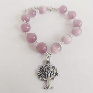 Armband boom bedeltje cateye lila. Armband met cateye kraaltjes in een lila kleur en een bedeltje in de vorm van een boompje. Er zit een verlengkettinkje aan zodat de armband verstelbaar is tot verschillende maten. De armband wordt getoond op een witte achtergrond.