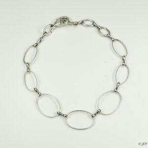 Armband schakels ovaal. Armband met ovale silver-plated schakels in verschillende grotes, met een bedeltje bij het slotje. Er zit een verlengkettinkje aan zodat de armband verstelbaar is tot verschillende maten. De armband wordt getoond op een witte achtergrond.