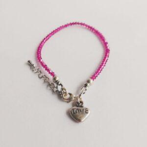 """Armband swarovski xilion 3 mm donker roze. Armbandje met kleine 3 mm hoekige (xilion) swarovski kraaltjes in de kleur fuchsia. Een donker roze kleur. Bij het slotje zit een leuk bedeltje in de vorm van een hartje met """"Love"""" erop. Er zit een verlengkettinkje aan zodat de armband verstelbaar is tot verschillende maten. De armband is te zien op een witte achtergrond."""