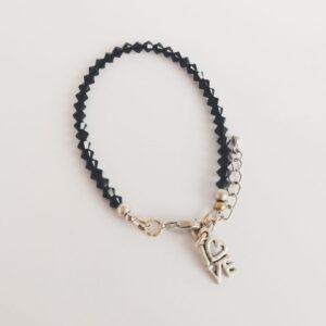 """Armband swarovski xilion zwart. Armbandje met kleine 4 mm hoekige (xilion) swarovski kraaltjes in de kleur jet. Een zwarte kleur. Bij het slotje zit een leuk bedeltje van het woord """"Love"""". Er zit een verlengkettinkje aan zodat de armband verstelbaar is tot verschillende maten. De armband wordt getoond op een witte achtergrond."""