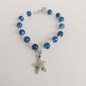 Armband zeester bedeltje glaskraaltjes blauw. Armband met glaskraaltjes in een blauwe kleur en een bedeltje in de vorm van een zeester. Er zit een verlengkettinkje aan zodat de armband verstelbaar is tot verschillende maten. De armband wordt getoond op een witte achtergrond.