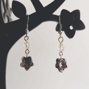 Oorbellen bloem bedeltje swarovski kristal. Oorbellen met een metalen bedeltje in de vorm van een bloem met erboven een Swarovski kraaltje, in de kleur crystal, een kristal kleur. Alle oorbellen zijn inclusief rubberen dopjes. De oorbellen worden getoond in een zwart kunststof sieraden boompje op een witte achtergrond.