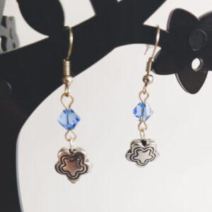 Oorbellen bloem bedeltje swarovski blauw. Oorbellen met een metalen bedeltje in de vorm van een bloem met erboven een Swarovski kraaltje, in de kleur crystal, een kristal kleur. Alle oorbellen zijn inclusief rubberen dopjes. De oorbellen worden getoond in een zwart kunststof sieraden boompje met een witte achtergrond.