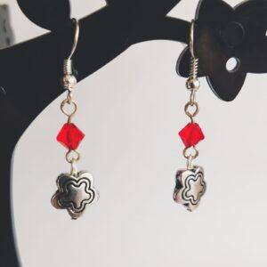 Oorbellen bloem bedeltje swarovski rood. Oorbellen met een metalen bedeltje in de vorm van een bloem met erboven een Swarovski kraaltje, in de kleur siam, een rode kleur. Alle oorbellen zijn inclusief rubberen dopjes. De oorbellen worden getoond in een zwart kunststof sieraden boompje met een witte achtergrond.