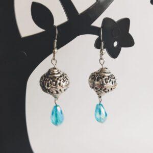 Oorbellen bohemian glaskraal blauw. Oorbellen met een metalen kraal met een facet geslepen glaskraaltje in een druppel vorm in een blauwe kleur. Alle oorbellen zijn inclusief rubberen dopjes. De oorbellen worden getoond in een zwart kunststof sieraden boompje met een witte achtergrond.