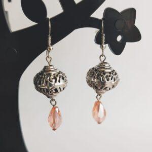 Oorbellen bohemian glaskraal roze. Oorbellen met een metalen kraal met een facet geslepen glaskraaltje in een druppel vorm in een roze kleur. Alle oorbellen zijn inclusief rubberen dopjes. De oorbellen worden getoond in een zwart kunststof sieraden boompje met een witte achtergrond.