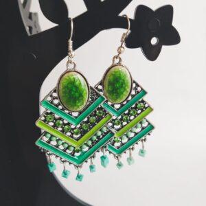 Oorbellen boho chic groen. Oorbellen van metaal met emaille en glas steentjes en kraaltjes in verschillende tinten groen. Alle oorbellen zijn inclusief rubberen dopjes. De oorbellen worden getoond in een zwart kunststof sieradenboompje met een witte achtergrond.