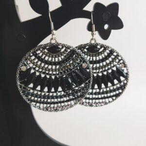 Oorbellen boho chic rond zwart. Oorbellen van metaal met emaille en glas steentjes en kraaltjes in zwart en grijs in een ronde vorm. Alle oorbellen zijn inclusief rubberen dopjes. De oorbellen worden getoond in een zwart kunststof sieraden boompje met een witte achtergrond.