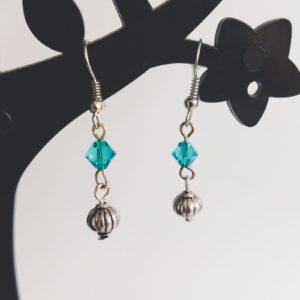 Oorbellen gedecoreerde kraal swarovski groen blauw. Oorbellen met een metalen gedecoreerd kraal met erboven een swarovski kraaltje, in de kleur blue zirkon, een groen blauwe kleur. Alle oorbellen zijn inclusief rubberen dopjes. De oorbellen worden getoond in een zwart kunststof sieraden boompje met een witte achtergrond.