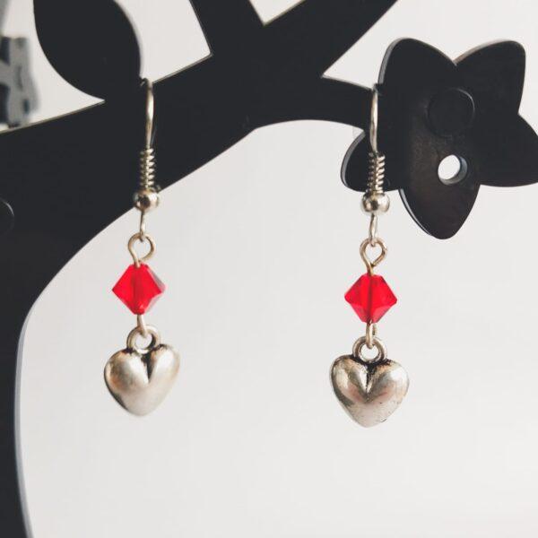 Oorbellen hart bedeltje swarovski rood. Oorbellen met een metalen hart bedeltje met erboven een swarovski kraaltje, in de kleur siam, een rode kleur. Alle oorbellen zijn inclusief rubberen dopjes. De oorbellen worden getoond in een zwart kunststof sieraden boompje met een witte achtergrond.
