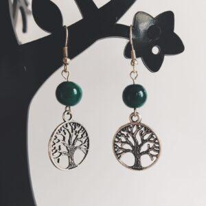 Oorbellen rond boom bedeltje glaskraal groen. Oorbellen met een rond boom bedeltje met erboven een glaskraal, in een groene kleur. Alle oorbellen zijn inclusief rubberen dopjes. De oorbellen worden getoond in een zwart kunststof sieraden boompje met een witte achtergrond.