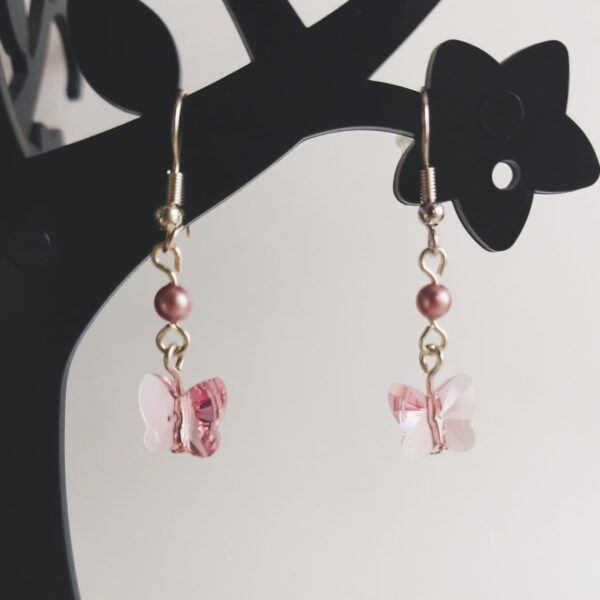 Oorbellen swarovski fancy stone vlinder roze. Oorbellen met een swarovski fancy stone in een vlinder vorm in de kleur light rose, een roze kleur. Met een swarovski pareltje in een roze kleur. Alle oorbellen zijn inclusief rubberen dopjes. De oorbellen worden getoond in een zwart kunststof sieraden boompje met een witte achtergrond.