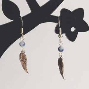 Oorbellen vleugel bedeltje natuursteen soldalite blauw. Oorbellen met een vleugel bedeltje met erboven een natuursteen soldalite kraaltje in de kleur blauw. Alle oorbellen zijn inclusief rubberen dopjes. De oorbellen worden getoond in een zwart kunststof sieraden boompje met een witte achtergrond.