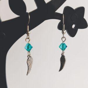 Oorbellen vleugel bedeltje swarovski groen blauw. Oorbellen met een vleugel bedeltje met erboven een swarovski kraaltje in de kleur blue zirkon, een groen blauwe kleur. Alle oorbellen zijn inclusief rubberen dopjes. De oorbellen worden getoond in een zwart kunststof sieraden boompje met een witte achtergrond.