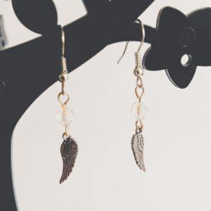 Oorbellen vleugel bedeltje swarovski kristal. Oorbellen met een vleugel bedeltje met erboven een swarovski kraaltje in de kleur crystal, een kristal kleur. Alle oorbellen zijn inclusief rubberen dopjes. De oorbellen worden getoond in een zwart kunststof sieraden boompje met een witte achtergrond.