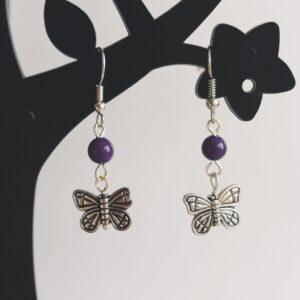 Oorbellen vlinder bedeltje glaskraaltjes paars. Oorbellen met een vlinder bedeltje met erboven een glaskraaltje in de kleur paars. Alle oorbellen zijn inclusief rubberen dopjes. De oorbellen worden getoond in een zwart kunststof sieraden boompje met een witte achtergrond.