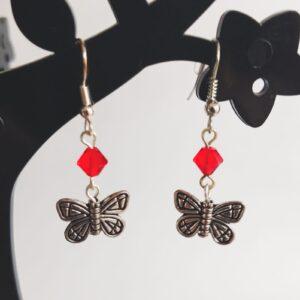 Oorbellen vlinder bedeltje swarovski rood. Oorbellen met een vlinder bedeltje met erboven een swarovski kraaltje in de kleur siam, een rode kleur. Alle oorbellen zijn inclusief rubberen dopjes. De oorbellen worden getoond in een zwart kunststof sieraden boompje met een witte achtergrond.