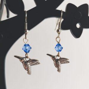 Oorbellen vogel bedeltje swarovski blauw. Oorbellen met een vlinder bedeltje met erboven een swarovski kraaltje in de kleur sapphire, een blauwe kleur. Alle oorbellen zijn inclusief rubberen dopjes. De oorbellen worden getoond in een zwart kunststof sieraden boompje met een witte achtergrond.