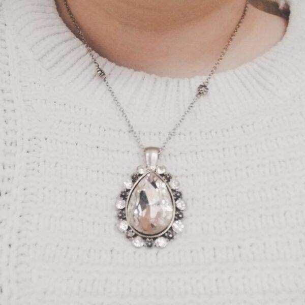 Ketting glamour bloemen glas kristal. Een dun metalen kettinkje met kleine metalen bloem kraaltjes en een hanger met een druppelvormige glassteen erin in de kleur kristal. Om de steen zijn kleine glas steentjes en bloemtjes gezet. Het kettinkje is 44 cm lang. De ketting is te zien om de hals van een blanke vrouw met een witte trui aan.