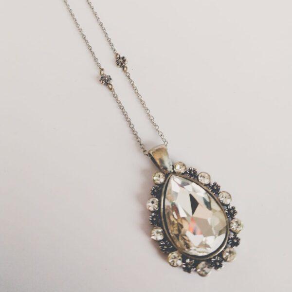 Ketting glamour bloemen glas kristal. Een dun metalen kettinkje met kleine metalen bloem kraaltjes en een hanger met een druppelvormige glassteen erin in de kleur kristal. Om de steen zijn kleine glas steentjes en bloemtjes gezet. Het kettinkje is 44 cm lang. De ketting is te zien op een witte achtergrond.