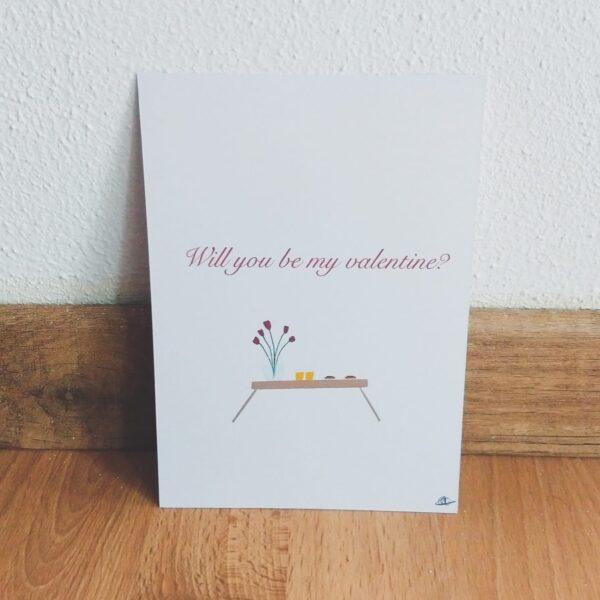 """Ansichtkaart valentijnsdag ontbijt op bed. Leuke ansichtkaart met een tekening van ontbijt op bed. Deze kaart heeft op de voorkant een mooie hand geillustreerde afbeelding van een bed tafeltje met een vaas met bloemen en ontbijt voor 2 erop. Erboven staat de tekst """"Will you be my valentine?""""."""