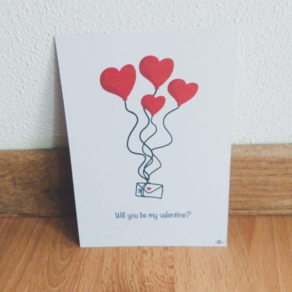 """Ansichtkaart valentijnsdag briefpost. Leuke ansichtkaart met een tekening van ballonen in de vorm van een hart, aan de balonnen hangen touwen waar liefdes post aan hangt, eronder staat de tekst """"Will you be my valentine?""""."""