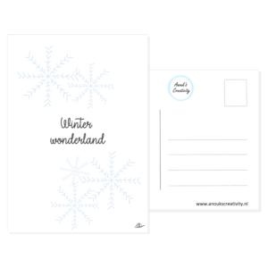 """Ansichtkaart winter wonderland. Leuke ansichtkaart met een tekening van een ijskristallen. Deze kaart heeft op de voorkant een mooie hand geillustreerde afbeelding van ijskristallen en de tekst """"Winter wonderland"""" ertussen. De kaart is te zien op een witte achtergrond, de achterkant van de kaart is ook te zien."""