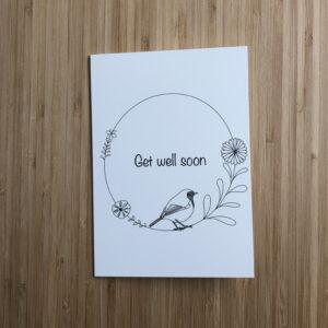 Wenskaart met cirkel met roodborstje, bloemen en blaadjes en de tekst Get well soon.