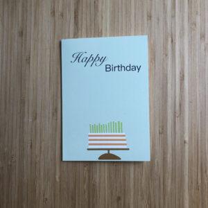 Wenskaart happy birthday cake, blauwe kaart met oranje wit gestreepte taart met groene kaarsjes.