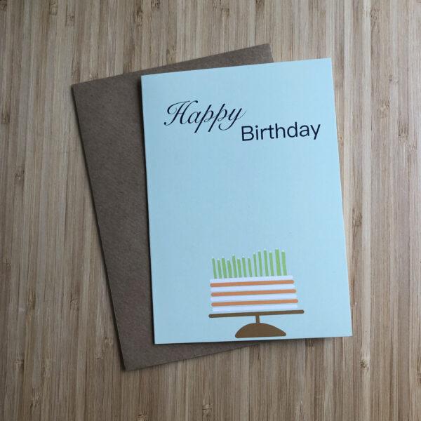 Wenskaart happy birthday cake, blauwe kaart met oranje wit gestreepte taart met groene kaarsjes. Met een kraft envelop