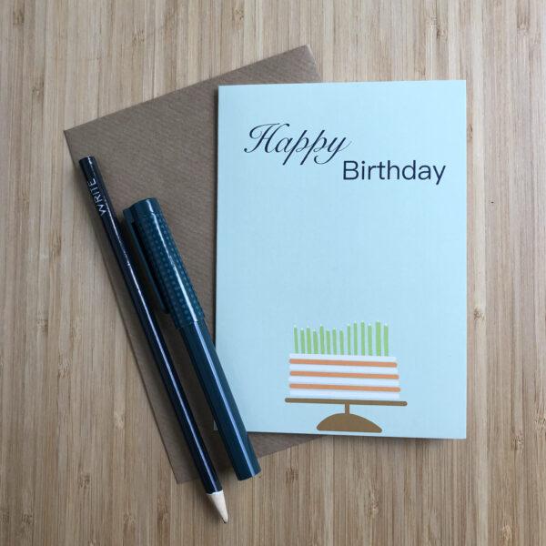 Wenskaart happy birthday cake, blauwe kaart met oranje wit gestreepte taart met groene kaarsjes. Met een kraft envelop en pen en potlood