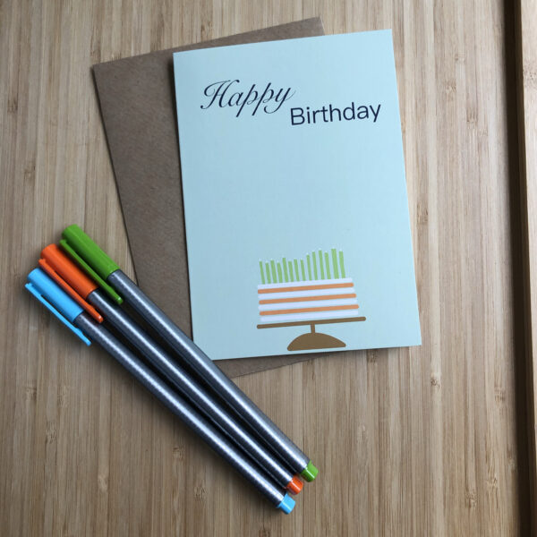 Wenskaart happy birthday cake, blauwe kaart met oranje wit gestreepte taart met groene kaarsjes. Met een kraft envelop en gekleurde pennen.