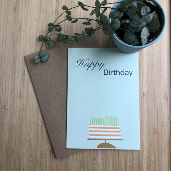 Wenskaart happy birthday cake, blauwe kaart met oranje wit gestreepte taart met groene kaarsjes. Met een kraft envelop en een plantje.